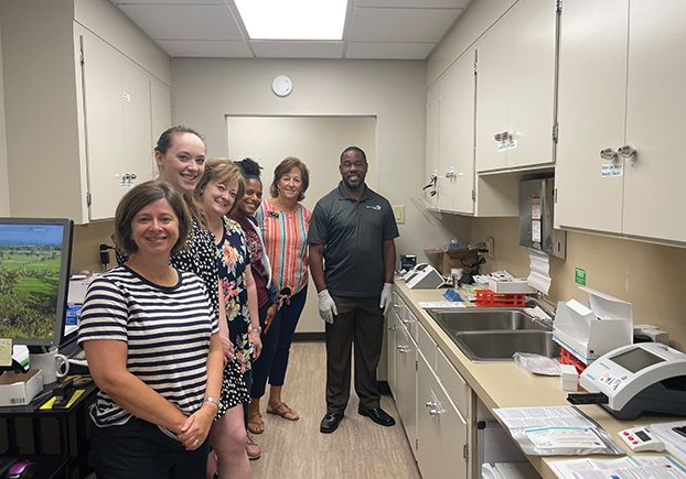Amy Wilson, Caroline Parrott, Cathy Teat, DeAnna Turner, Krista Woolly, and a training representative stand next to the testing machine and supplies provided through the grant. Photo submitted.